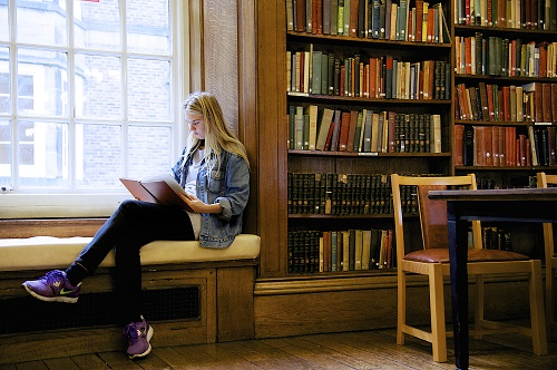 Girl sitting and reading in the library